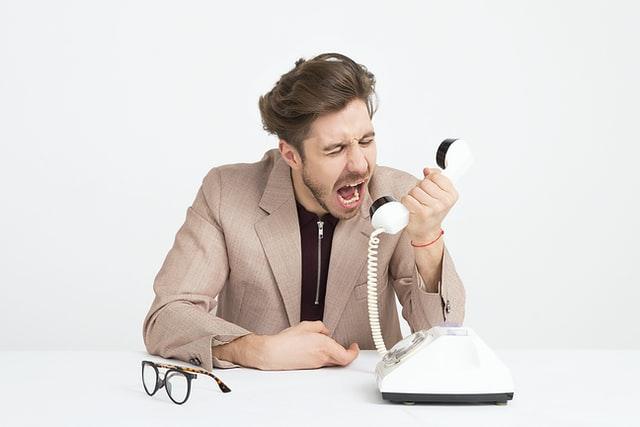 言うことを聞かない部下に厳しく指導の電話をする上司