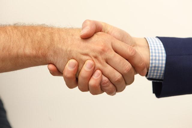 威圧的なお客様との営業で信頼を築き、握手する営業マンの様子
